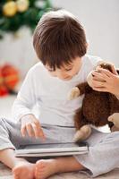 menino bonitinho e seu brinquedo macaco, jogando no tablet foto
