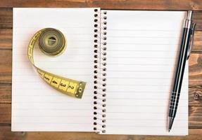 bloco de notas com centímetro e caneta