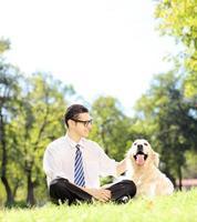 sorridente jovem empresário com seu cachorro sentado no parque foto