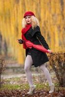linda jovem elegante com acessórios vermelhos no parque outonal foto