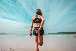atlética jovem alongamento na praia foto