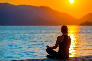 menina em posição de lótus, admirando o sol nascente foto