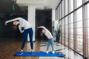mãe e filha fazendo yoga em casa foto