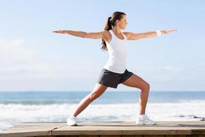 jovem mulher fazendo yoga na praia foto