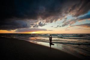 sessão de ioga de praia pelo mar polonês foto
