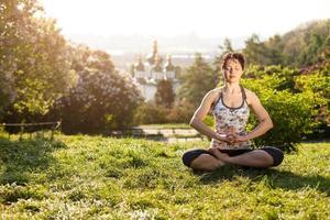 jovem mulher meditando na posição de lótus ao ar livre foto