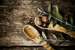 colheres de madeira de oliveira com azeitonas frescas foto
