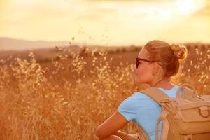 desfrutando de campo de trigo no pôr do sol