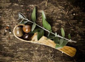 azeitonas frescas em uma colher de madeira verde-oliva foto