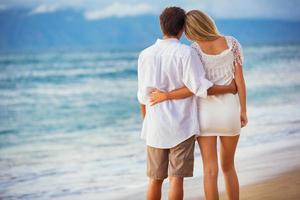 casal aproveitando o pôr do sol na praia foto