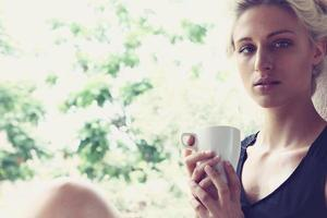 mulher bonita, desfrutando de seu café da manhã foto