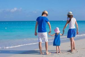 família feliz de três curtindo férias de praia foto