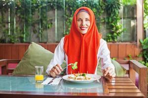 mulher muçulmana, desfrutando de suco e comida halal foto