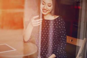 linda jovem gosta de telefone e tablet foto