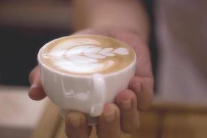 jovem encantadora desfrutando aroma café no café foto