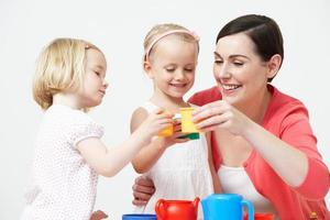 pré-escolares, desfrutando de festa do chá com o professor