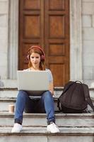 feliz desfrutando mulher ouvindo com fones de ouvido para música foto