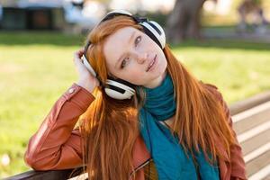 jovem encantadora relaxada curtindo música em fones de ouvido foto