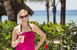 mulher, desfrutando de uma bebida na praia foto