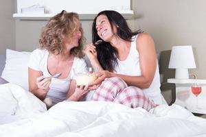 duas mulheres atraentes, aproveitando a noite de suas mulheres na cama foto