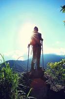 torcendo alpinista mulher apreciar a vista no penhasco de pico de montanha foto