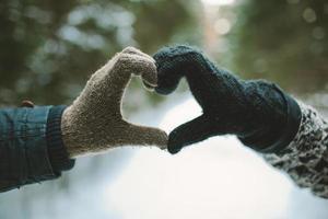 duas mãos em luvas segurando o símbolo do coração de amor foto