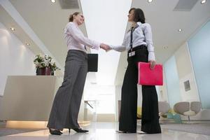 duas empresárias apertando as mãos no lobby, sorrindo, nível da superfície