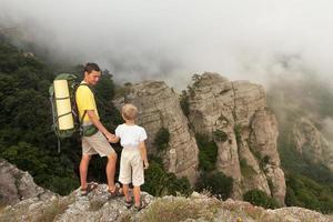 mochileiro com filho pequeno nas montanhas de nevoeiro. foto