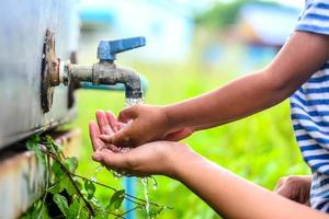 garoto lavando as mãos com a mãe, ponto de foco seletivo. foto