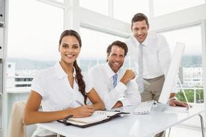 três empresários sorridentes na mesa de escritório