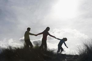 família dando as mãos enquanto caminhava na praia foto