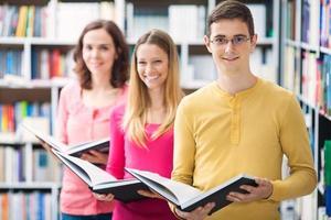 grupo de três pessoas na biblioteca foto