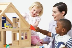 professor de pré-escola e alunos brincando com casa de madeira foto