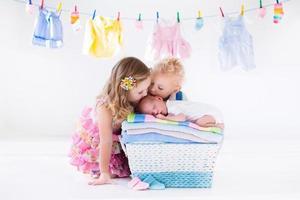 irmão e irmã beijando bebê recém-nascido