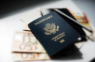 passaporte e dinheiro em cima da mesa foto