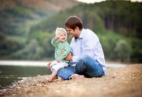 pai e filho à beira do lago foto