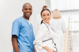 dois médicos alegres olhando por cima do ombro e sorrindo enquanto o