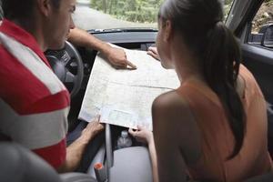casal com mapa no carro foto