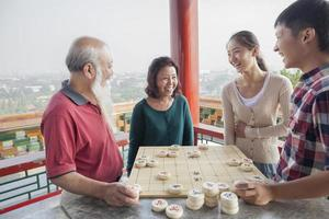família jogando xadrez chinês (xiang qi) foto