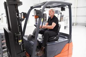 motorista de caminhão de garfo masculino trabalhando na fábrica foto