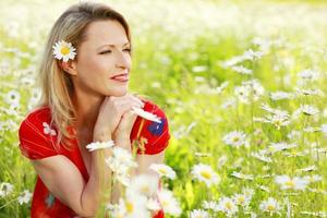 mulher sorridente no campo de margarida selvagem foto