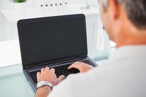 homem com cabelos grisalhos, digitando no laptop foto