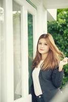 Ásia confiante jovem empresária em terno de mãos dadas no cabelo foto