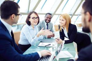 três homens e duas mulheres em trajes profissionais, tendo uma reunião foto