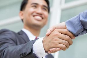 homem de negócios asiático fazendo aperto de mão com cara sorridente foto