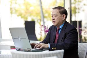 empresário asiático usando laptop pc foto