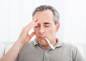 homem doente maduro com um termômetro na boca foto