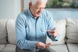 homem doente sênior tomando pílula foto