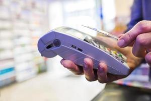 homem pagando na farmácia com tecnologia nfc foto