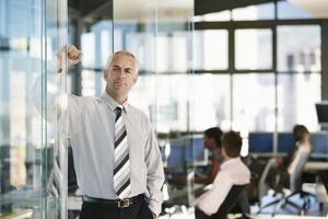 empresário confiante, apoiando-se na porta de vidro foto